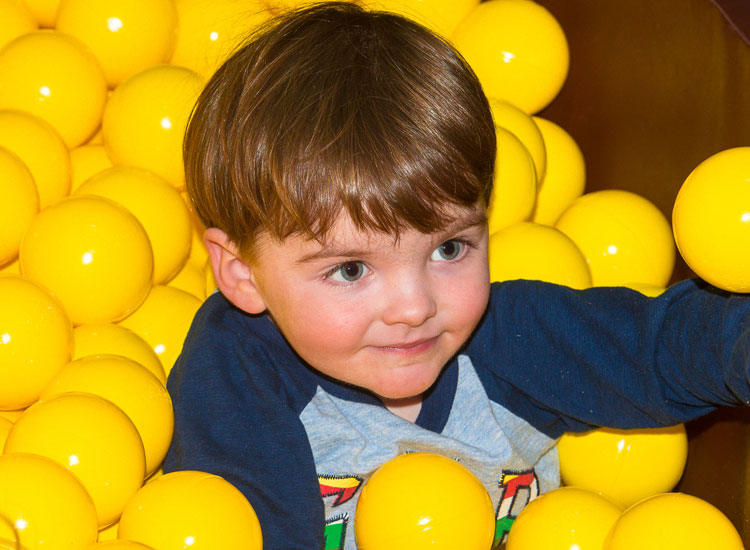 Toddler in ball pond at Dino Soft Play