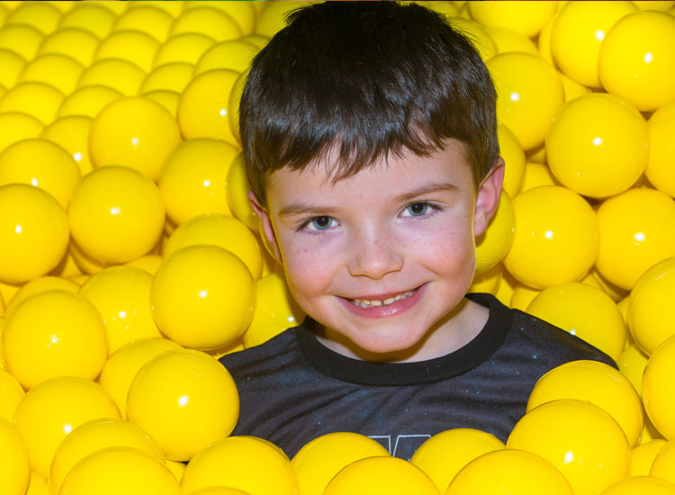 Little boy in a ball pond at Dino Soft Play
