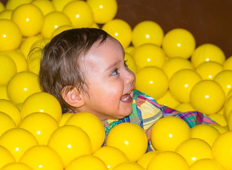 Baby in Dino Soft Play Ball Pond